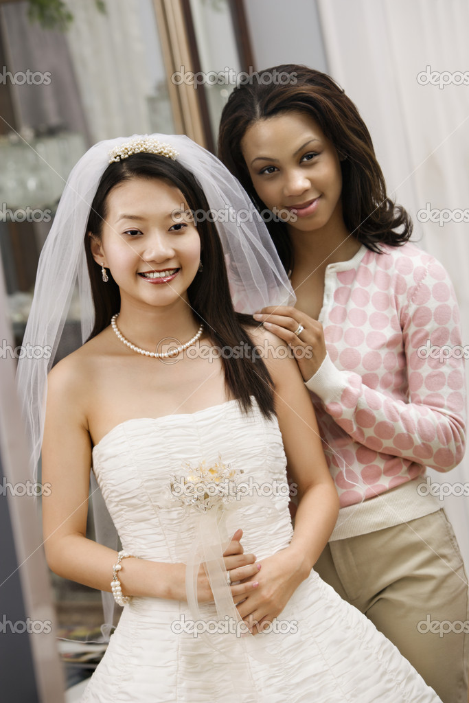 Asian bride and African-American friend admiring dress in mirror. — Stock Photo #9227464