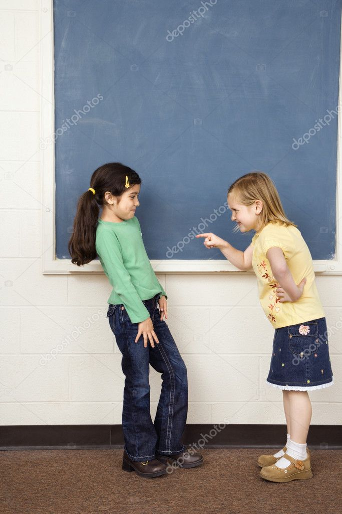 Girl pointing finger at other girl in school classroom. Vertically framed shot.  Stock Photo #9228312