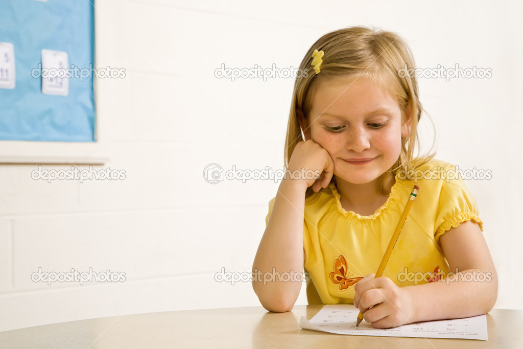Young girl smiling in classroom writing on paper. Horizontally framed shot.  Stock Photo #9228332
