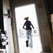 Woman running out door. - Stock Photo