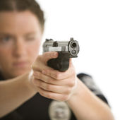 Policewoman aiming gun. — Stock Photo