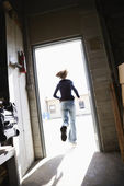 Woman running out door. — Stock Photo