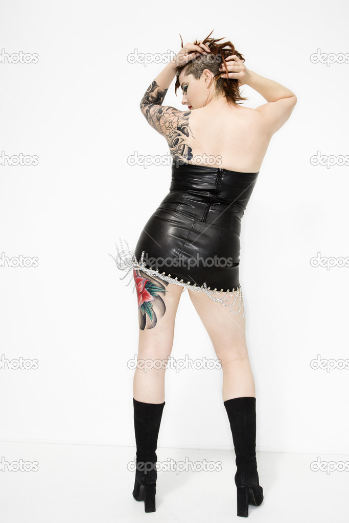 Back of adult tattooed caucasian female in leather dress. — Zdjęcie stockowe #9239838