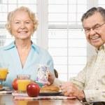 Mature couple eating breakfast. — Stock Photo