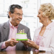 Mature couple with cake. — Stock Photo