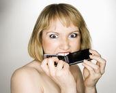Woman biting phone. — Stock Photo