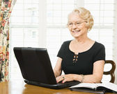 Mature woman with laptop. — Stock Photo