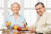 Mature couple eating breakfast. — Stock Photo