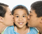 Parents kissing girl. — Stock Photo