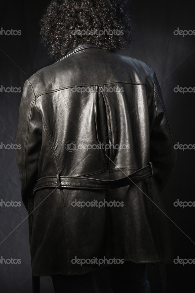 Back view of woman with curly hair wearing black leather jacket.  Stock Photo #9247493