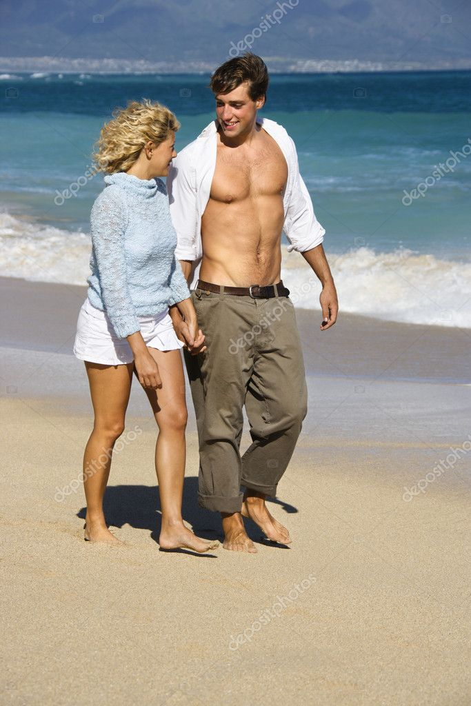 Attractive couple holding hands walking on beach smiling at eachother in Maui, Hawaii. — Stock Photo #9248003