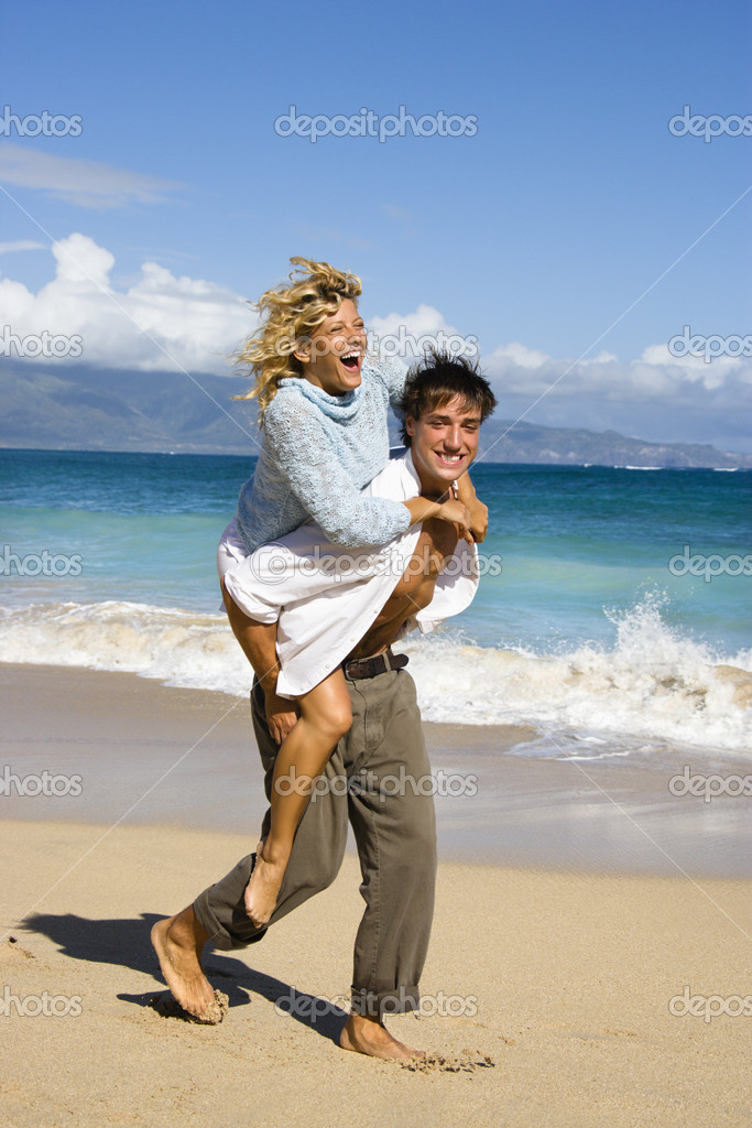 Woman riding piggyback on man while both smile and laugh on Maui, Hawaii beach.  Stock Photo #9248022