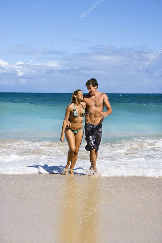 Attractive couple embracing and smiling as they walk out of water in Maui, Hawaii. — Stock Photo #9248102