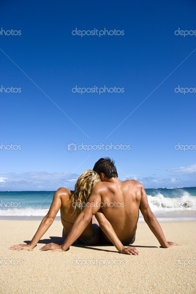 Couple sitting close together on Maui, Hawaii beach looking out at ocean. — Stock Photo #9248114