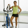 Woman with exercise bicycle. — Stock Photo
