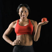 Athletic woman holding apple. — Stock Photo