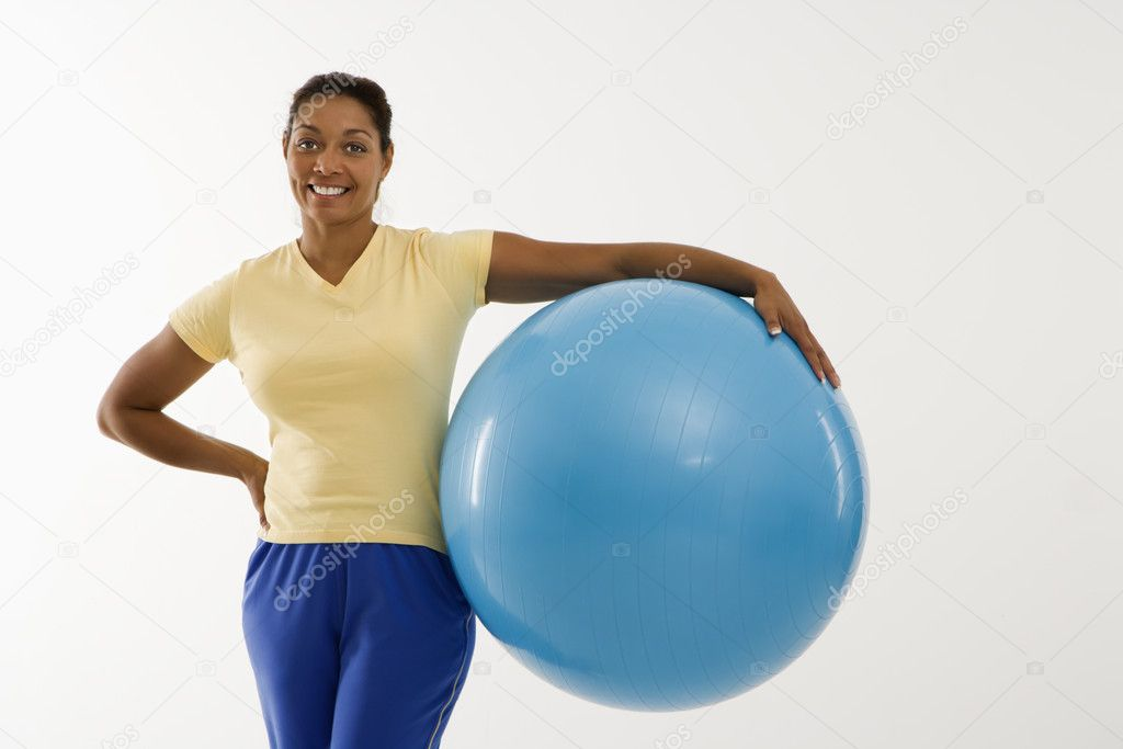 Mid adult multiethnic woman standing and holding blue exercise ball looking at viewer and smiling.  Stock Photo #9254063