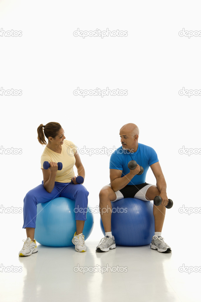 Mid adult multiethnic man and woman balancing on blue exercise balls while working out with dumbbells. — Stock Photo #9254080
