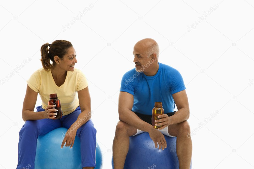 Mid adult multiethnic man and woman sitting on blue exercise balls looking at each other. — Stock Photo #9254089
