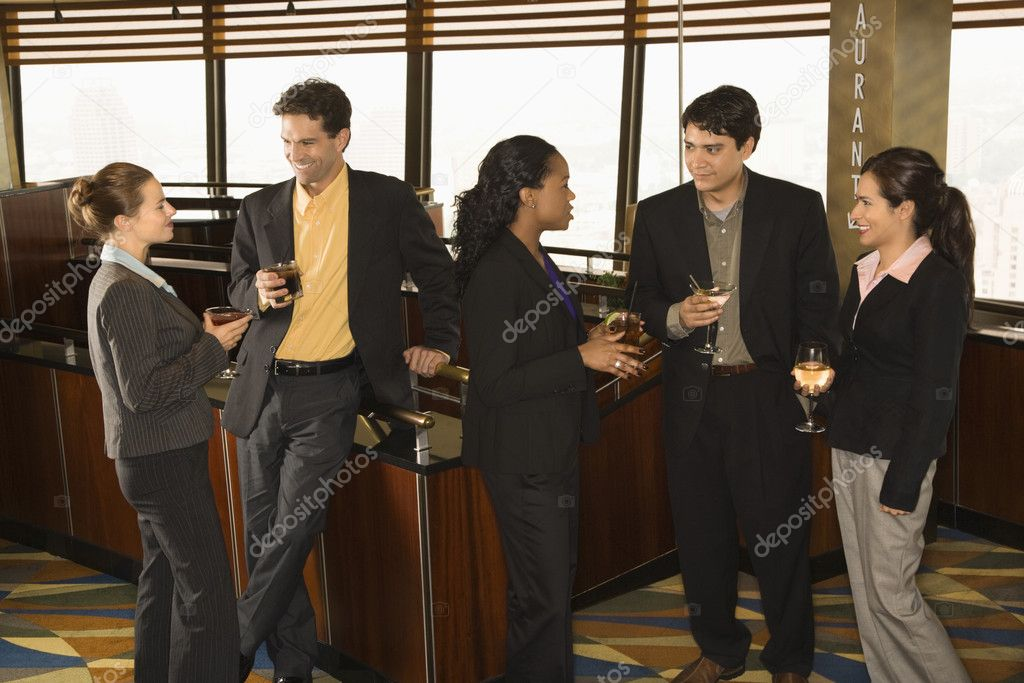 Ethnically diverse group of businesspeople in bar drinking and conversing. — Stock Photo #9255204