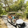 Family in golf cart. - Stock Photo
