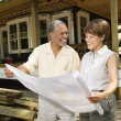 Stock Photo: Couple Holding Building Plans