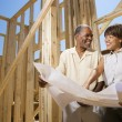 Couple Holding Building Plans on Construction Site — Stock Photo