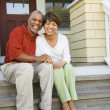 Couple Sitting on Outdoor Steps of Home Smiling - Stock Photo