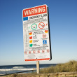 Warning sign on beach. — Stock Photo