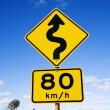 Speed limit curve ahead sign - Stock Photo