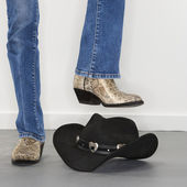 Boots stomping cowboy hat. — Stock Photo