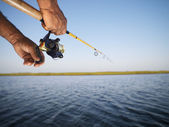 Hands holding fishing pole. — Stock Photo