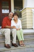Pár sedící na venkovních schodech domů s úsměvem — Stock fotografie