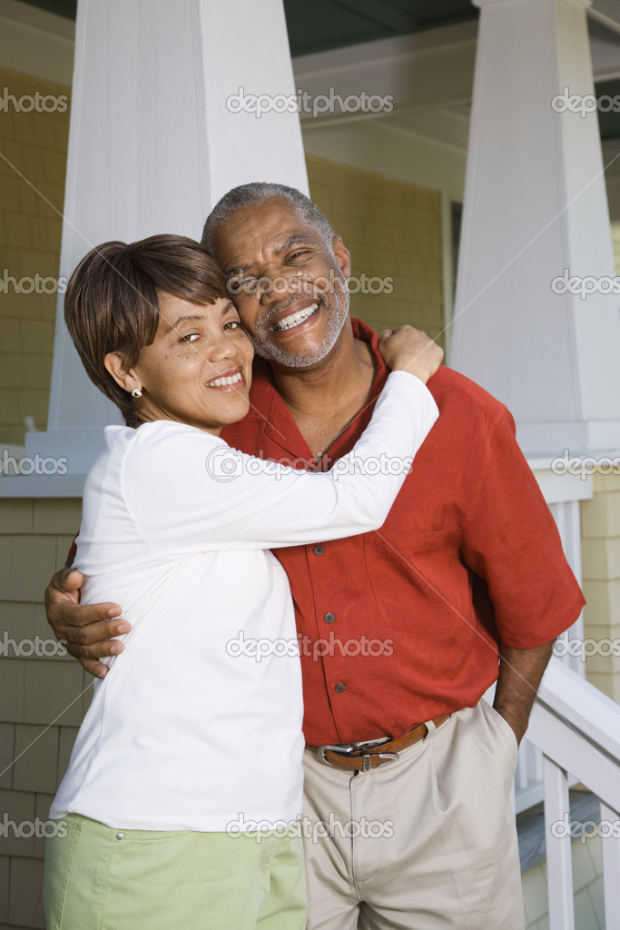 African American middle aged couple hugging and smiling at viewer.  Stock Photo #9276956