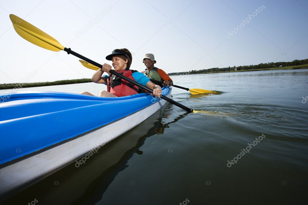 Low angle of African American middle-aged man and woman paddling kayak.  Stock Photo #9276982