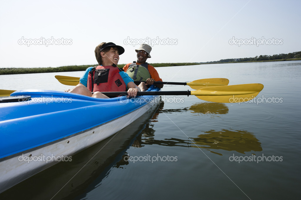 African American middle-aged couple sitting in kayak on lake smiling and laughing. — Stock Photo #9276985