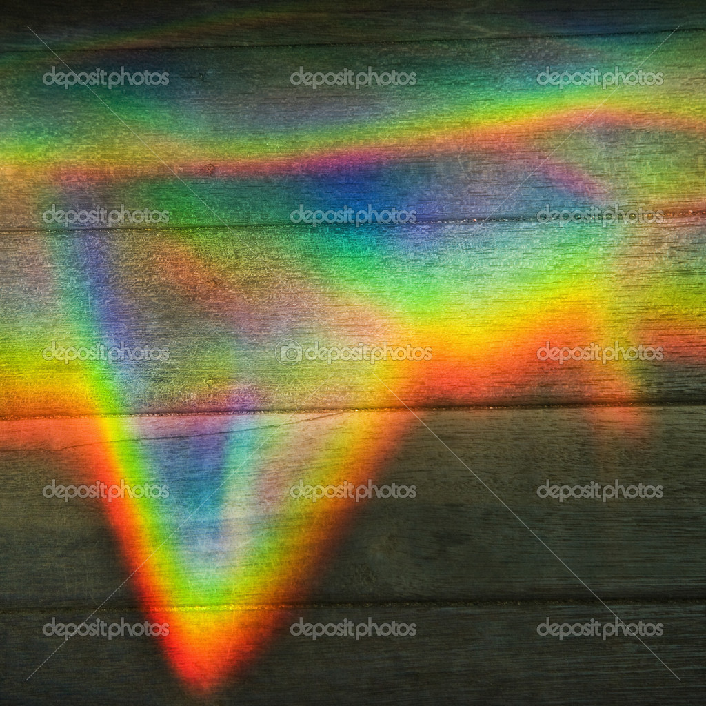 Abstract design of rainbow color prism on wood paneling. — Stock Photo #9277231