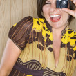 Woman and miniature camera. — Stock Photo