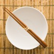 Stock Photo: Chopsticks on an Empty Bowl