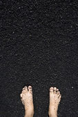 Barefeet in black sand. — Stock Photo
