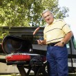Senior man grilling by RV. - Stock Photo