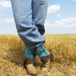 Cowboy standing in field. - Stock Photo