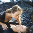 Attractive Young Couple Lying on Rocks — Stock Photo