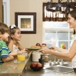Mom giving kids breakfast. — Stock Photo #9305963