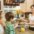 Mom giving kids breakfast. — Stock Photo