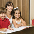 Mom and kids with homework. - Stock Photo
