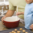 Stock Photo: Dad and son making cookies.