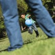 Son kicking ball to dad. - Stock Photo