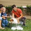 Family giving dog a bath. — Stock Photo #9306556