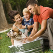 Family giving dog a bath. — Stock Photo